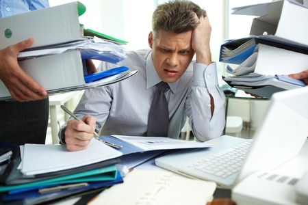 Perplexed accountant doing financial reports being surrounded by business partners with huge piles of documents Stock Photo - 13475851