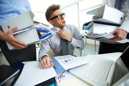 workaholic: Shocked accountant looking at huge piles of documents held by his partners