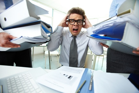 the bookkeeper: Terrified accountant touching his head being surrounded by huge piles of documents and screaming