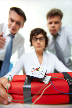 Close-up of dynamite with group of businesspeople on background Stock Photo - 13475828