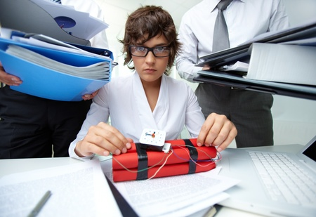 Serious secretary with dynamite being surrounded by big heaps of papers Stock Photo - 13475886