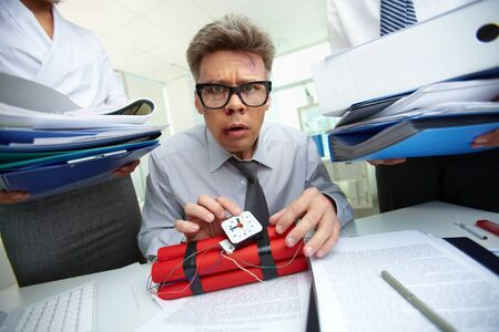 Serious accountant with dynamite being surrounded by big heaps of papers Stock Photo - 13475888