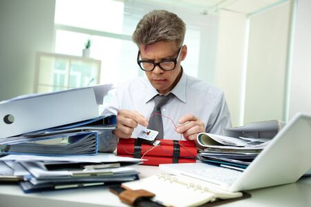 Serious accountant surrounded by big heaps of papers making dynamite photo