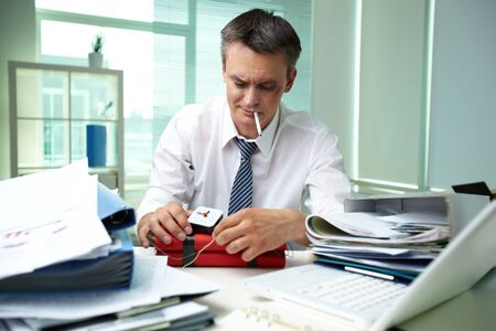 experienced: Experienced businessman surrounded by big heaps of papers making dynamite Stock Photo