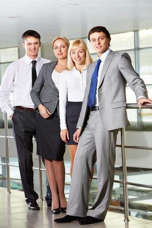 companionship: Retrato de cuatro hombres de negocios sonrientes mirando a la cámara