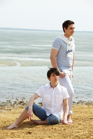 Vertical shot of young homosexuals resting at beach together photo