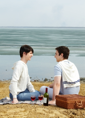 Gay couple having a romantic picnic on a sunny spring day photo