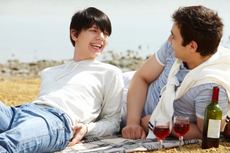 Laughing gay couple having a good time drinking red wine at beach photo