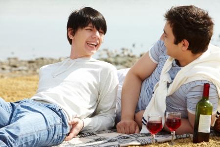 homosexuales: Riendo pareja gay que tiene un vino de color rojo el tiempo para beber un buen en la playa