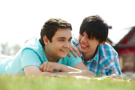 hombres gays: Felices los amantes homosexuales que yacen sobre el c�sped Foto de archivo