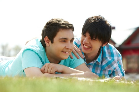 gay men: Happy gay lovers lying on the lawn