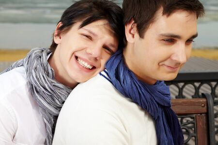 Portrait of smiling homosexual lovers dressed in elegant casual spending time outdoors photo
