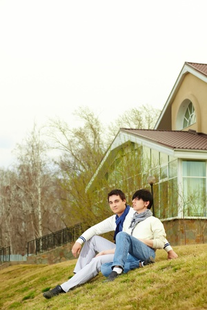 Gay couple sitting on a grassy slope of the hill in front of the townhouse photo