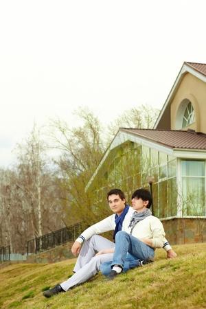 homosexuales: Pareja gay se sienta en una ladera cubierta de hierba de la colina frente a la casa Foto de archivo