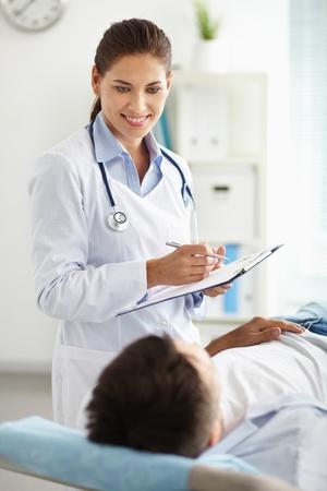 patient doctor: Sonriente mujer m�dico en busca de un paciente de la tumbada en el sof� Foto de archivo