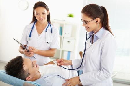 medico con paciente: Sonriente m�dico examinar al paciente, su asistente tomar notas Foto de archivo