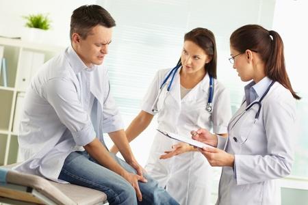 de rodillas: Pacientes que sufren de dolor en la pierna siendo examinado por una doctora y su asistente