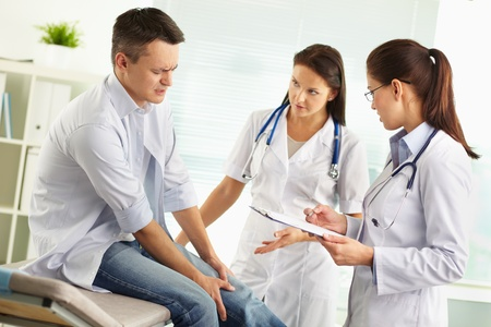 practise: Patient suffering from pain in the leg being examined by a female doctor and her assistant Stock Photo