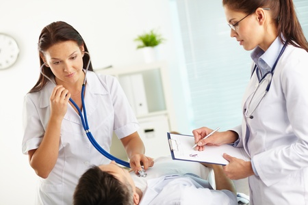 internals: Doctor listening to the patient�s internals using stethoscope, nurse taking notes