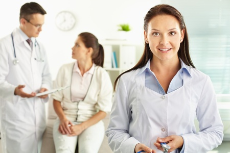 Beautiful lady doctor in the foreground smiling at camera, her colleague and a female patient talking about the symptoms Stock Photo - 13476029