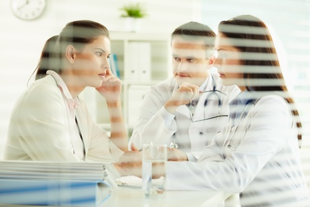 serious doctor: Unhappy female patient sitting in the doctor's office, practitioners taking care of her Stock Photo