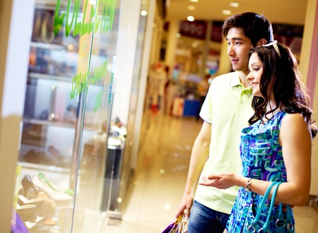 happy shopper: Tilt up of young couple standing in front of the shop window and looking at the merchandise Stock Photo