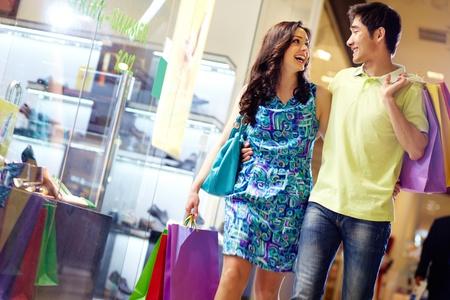 plaza comercial: Caminar vestido de manera informal hermosa pareja por el centro comercial que lleva un mont�n de bolsas de la compra