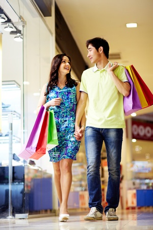 Vertical shot of attractive young people doing shopping together photo