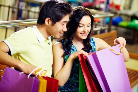happy shopping: Young woman and her boyfriend looking in the shopping bag with sweet anticipation Stock Photo