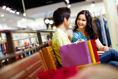 chicas de compras: Linda pareja sentada en un banco en el centro comercial y admirar uno al otro Foto de archivo