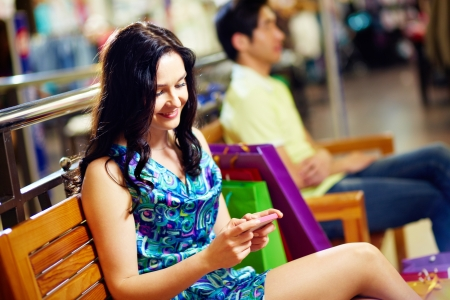Sweet lady typing a short message on her mobile phone, her male friend can be seen in the background, shopping series photo