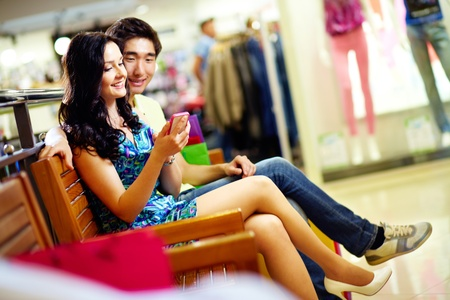 friends shopping: Young people using a smart phone in the shopping mall, shopping series