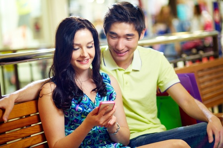 interested: Young people sitting together, girl holding a mobile phone