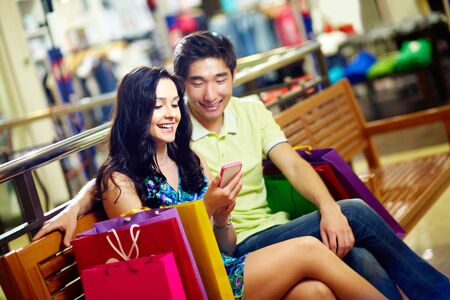 Tilt up of a happy couple using the mobile for quick and convenient communication in shopping mall photo