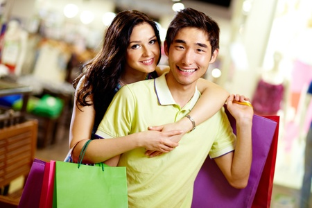 shopaholism: Portrait of cheerful shopping couple smiling at cam