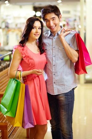 jovenes enamorados: Pareja romántica con bolsas de compras posando delante de la cámara con una sonrisa