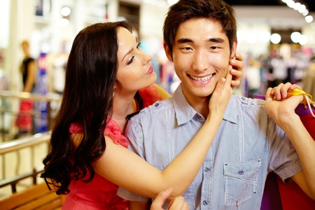 Girl being about to kiss her boyfriend smiling at cam, shopping series photo