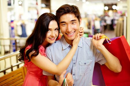 tenderly: Beautiful girl hugging tenderly her boyfriend with shopping bags