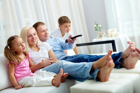 home comfort: Portrait of happy family with two children sitting on sofa and watching TV Stock Photo