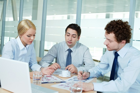 Business people gathered to discuss documents Stock Photo - 13589706