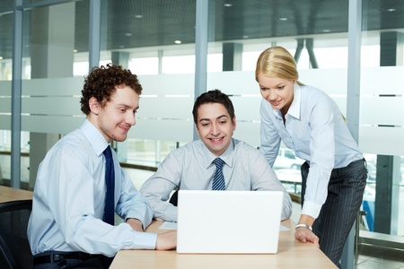 Business people gathered in office in front of laptop Stock Photo - 13589713