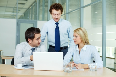 Business people gathered in office in front of laptop Stock Photo - 13589698