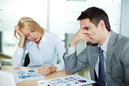environment issues: Sad business partners at workplace, focus is on confused male