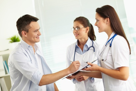 Portrait of confident female doctors consulting patient in hospital photo
