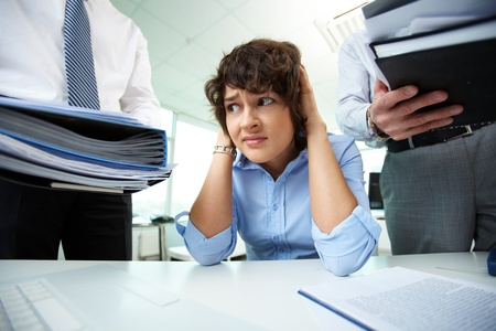 Terrified secretary touching her head while looking at big heaps of papers photo