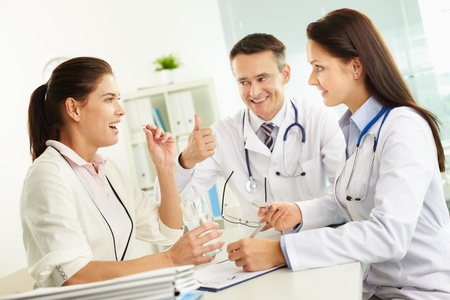 Portrait of confident practitioners prescribing tablets to patient in hospital photo