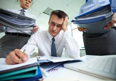 persona confundida: Perplejo contador haciendo los informes financieros de estar rodeado de socios de negocios con enormes pilas de documentos Foto de archivo