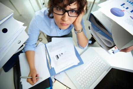 persona confundida: Contador perplejos mirando a la c�mara mientras hace los informes financieros