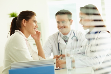 Portrait of confident practitioners consulting patient in hospital Stock Photo - 13589849