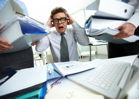 Terrified accountant touching his head being surrounded by huge piles of documents and screaming